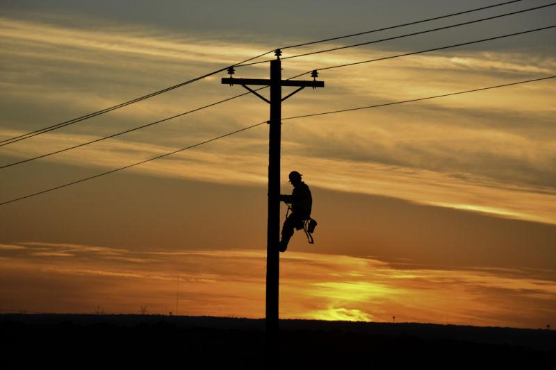 Lineman on pole during sunset