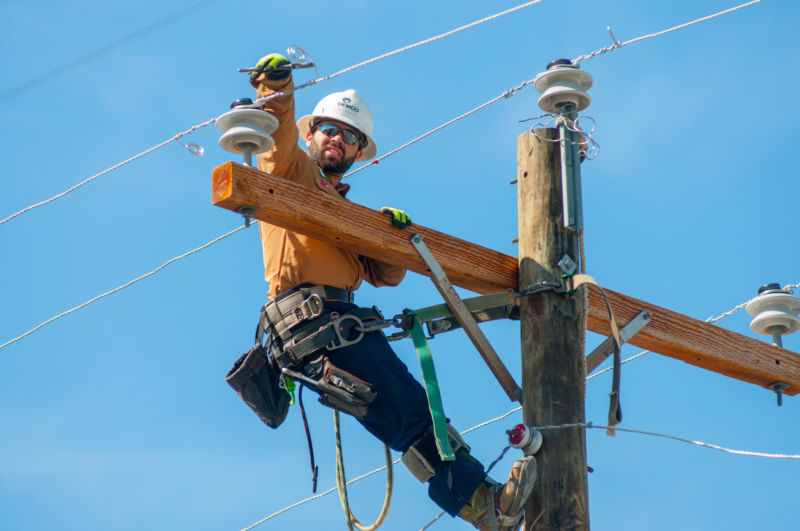 Lineman in an orange shirt and personal protective equipment working on a power line