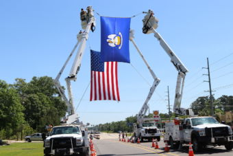 Louisiana State flag and US Flag hung from Electrical boom trucks
