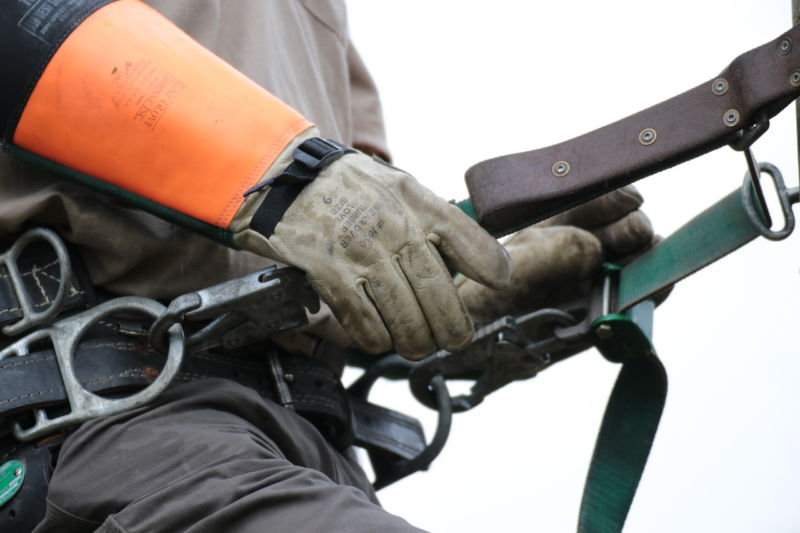 Up close of linemans hands in orange gloves, holding onto attached safety harness
